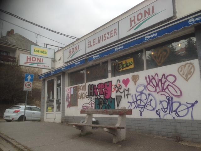 A bezárt Honi közért a Hegyalja út és a Sashegyi út találkozásánál Mécsesek a Honi bejáratánál (fotó: ittlakunk.hu)